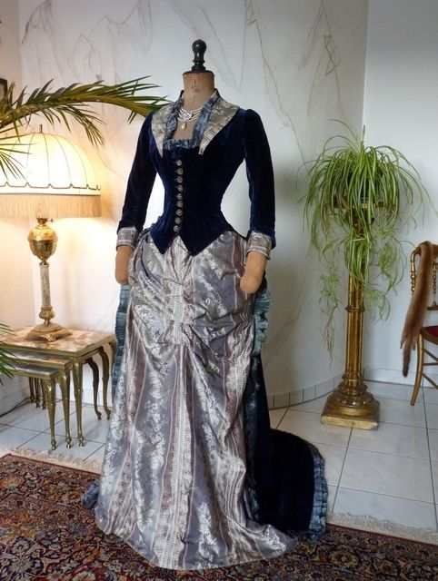 Sapphire blue velvet reception dress, 1878, American.  One-piece velvet gown w/ train swept back over bustle.  Skirt is gray & mauve striped silk w/ cream floral brocade, trimmed w/ blue satin double ruffle.  Collar & cuffs of the skirt fabric.