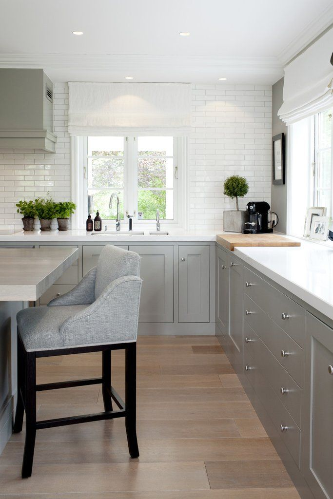 Another gorgeous grey kitchen! Loving how the wall and vent hood were painted to match the cabinets - they really pop against the white backsplash and counte