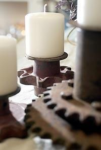 Old farm equipment gears are used as a base for candleholders