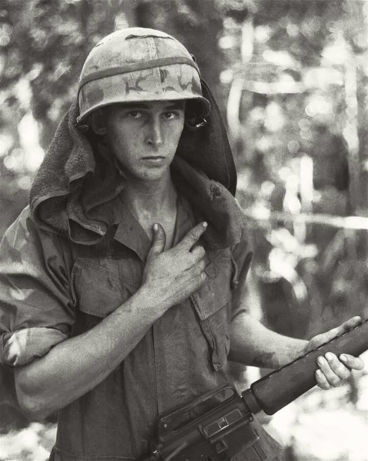 Looks to me that this soldier is pointing to the hole in his towel. Maybe a close call from a sniper. ~ Vietnam War