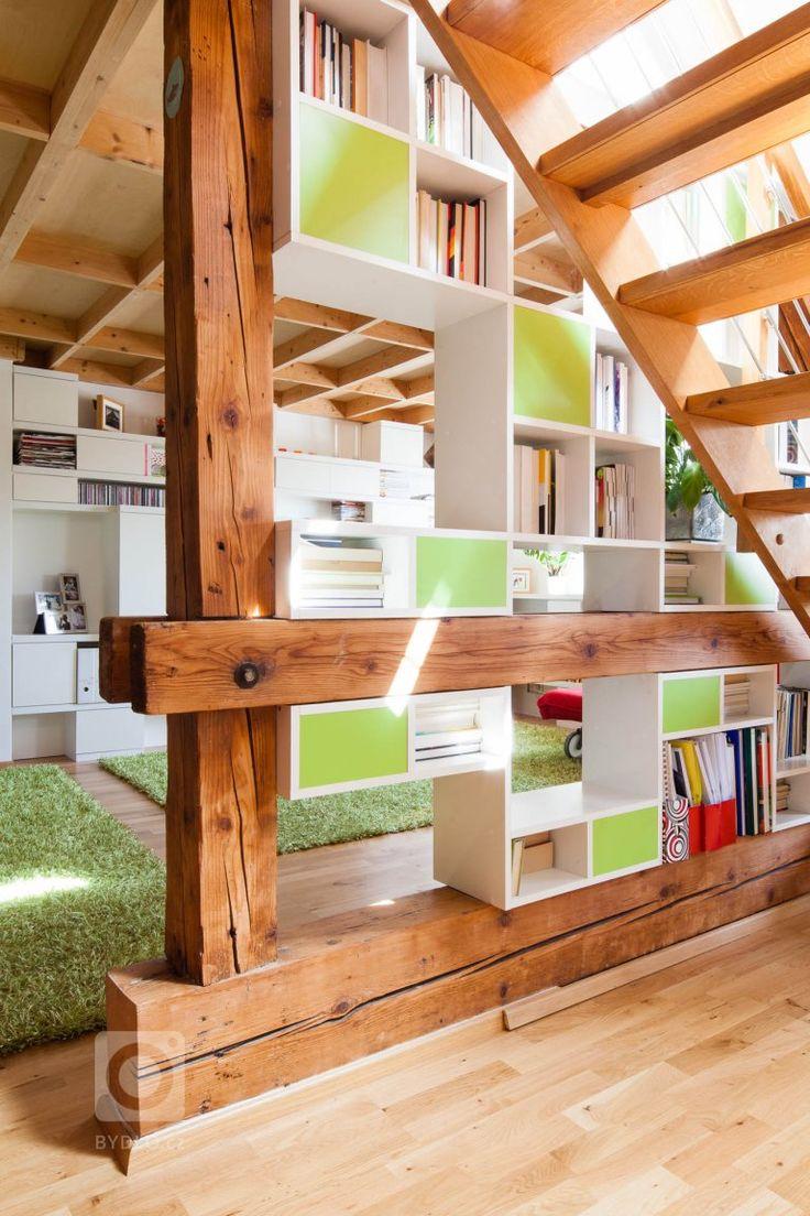 Knihovna je vložena do trámoví podkrovního bytu, odděluje prostor obývacího pokoje a kuchyně, ale zároveň ponechává vizuální kontakt. Ortogonální rastr otvorů…