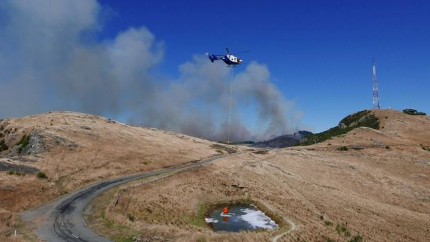 A helicopter fills a monsoon bucket from a small pond near Sugarloaf on the Port Hills.