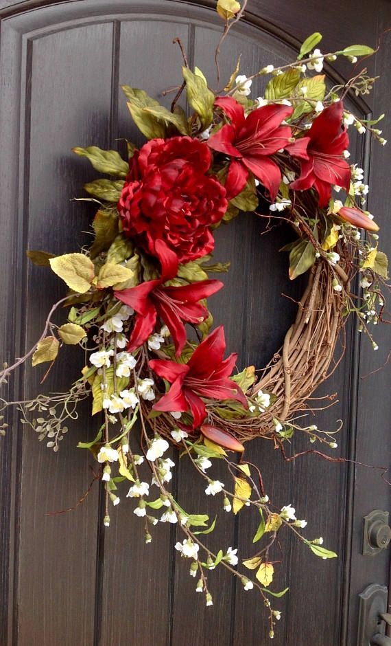 An original design by An Extraordinary Gift © This lily design is just stunning! I adore the welcoming fresh feel this design gives off. This design is created with peony foliage branches, red lilies, and a gorgeous red peony. I love the added natural feel of the white flowering
