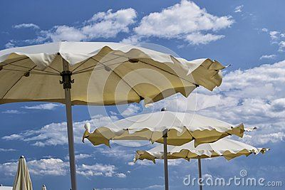 White parasols with blue sky and clouds. for summer seascape concept