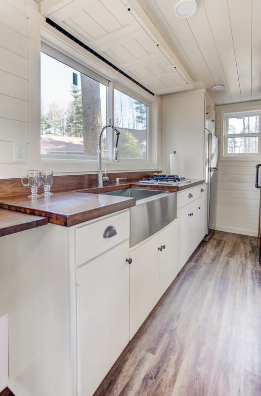 """The brown maple butcher block kitchen counter comes with a removable sink cutting board. The kitchen also includes a 32"""" farm sink, three burner propane cooktop, a counter/table extension, and an apartment size refrigerator."""