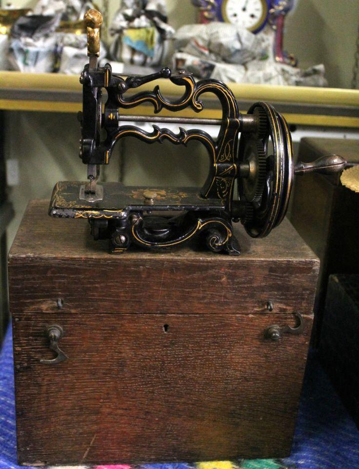 Macchina da cucire portatile 1880. Reinaudo Antichità, bottega di via Borgo Dora 12, offre un'ampia gamma di pezzi di antiquariato, dalle librerie alle cornici, dai mobili d'epoca agli strumenti scientifici.