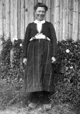 Digitalt Museum - Fru Tarjgjerd Hellesvik står utenfor en husvegg. Eiken, Hægesbostad, Vest-Agder 1937.
