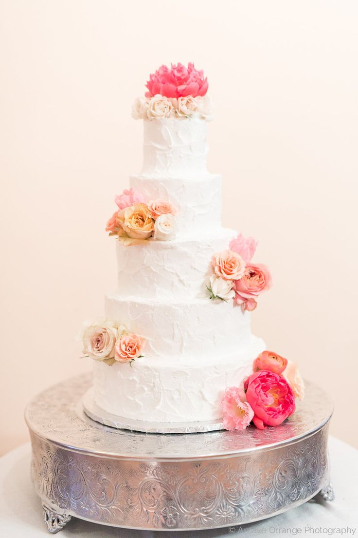 classic five tiered wedding cake is adorned with clusters of fresh spring flowers including coral charm peonies, white spray roses, peach ranunculus, peach spray pink tulips, and pink roses.