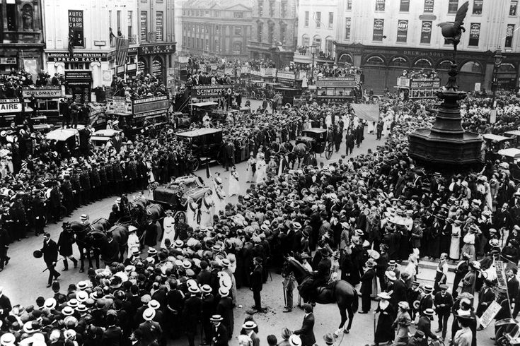 14 June 1913: Crowds watch the cortege of suffragette Emily Davison, who was killed by the King's horse at the Derby, passing Eros at Piccadilly Circus.