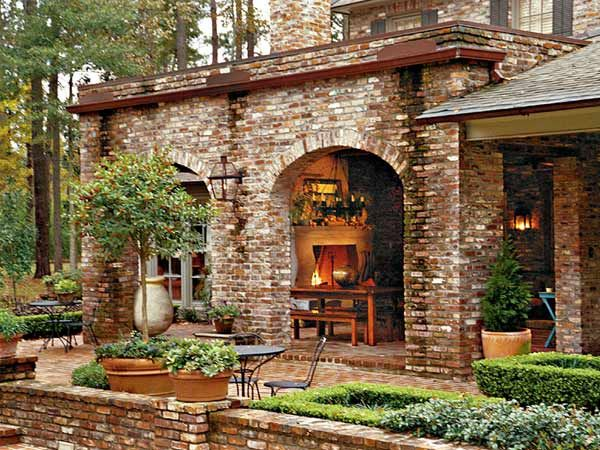 This backyard veranda serves as a fireside retreat. With views of lush landscaping and ancient live oaks, the covered terrace evokes the laid-back ambiance of the Mississippi River Delta.