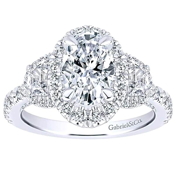 "Oval Halo Diamond Engagement Ring Featuring Half Moon & Round Cut Diamonds Weighing 1.56 Carats Total Weight in 18K White Gold. ""Willow"" by Gabriel available at BenGarelick.com https://www.bengarelick.com/products/gabriel-oval-cut-side-half-moon-diamond-engagement-ring"