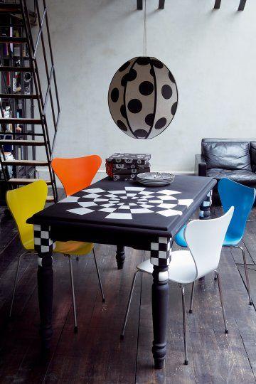 Une table en bois peinte en noir avec damier comme une cible noire et blanche au milieu