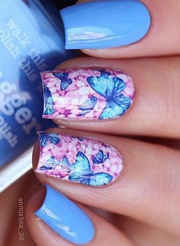 Enthralling butterfly nail art. The light blue colors of the design make the butterflies look magical and mystical the purple background also help emphasize the butterflies painted above it.