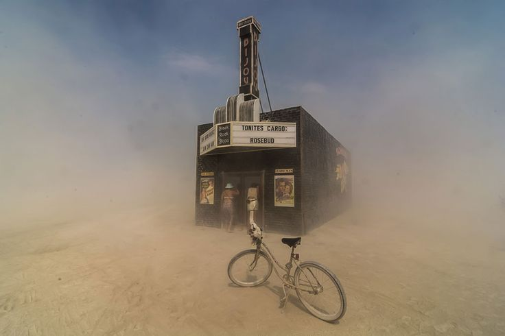 "Dust swirls around citizens of Black Rock City as they peek into the ""Black Rock Bijou Theatre,"" an art installation at the 2013 Burning Man festival. - by Mark Kaplan"