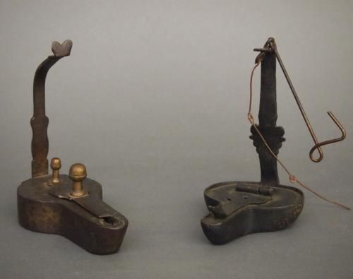Two late 18th/early 19th century wrought iron grease lamps. One with Brass finials. Old surface and some oxidation, one without hanger, the other with replace