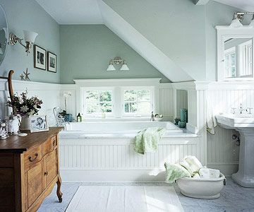 Bath 4 - This classically fresh bathroom looks as if the eave was planned into the design.  The tub nestles in the nook creating a cozy place to soak away.  Trimmed with beaded board and painted a soft spa blue-green, it's a comfortable retreat. Note the Carrara marble floor for luxurious details.  The central window provides a view of the lush garden beyond.  Both Mom's are sure to enjoy this lovely traditional, yet fresh design. #bhg.com