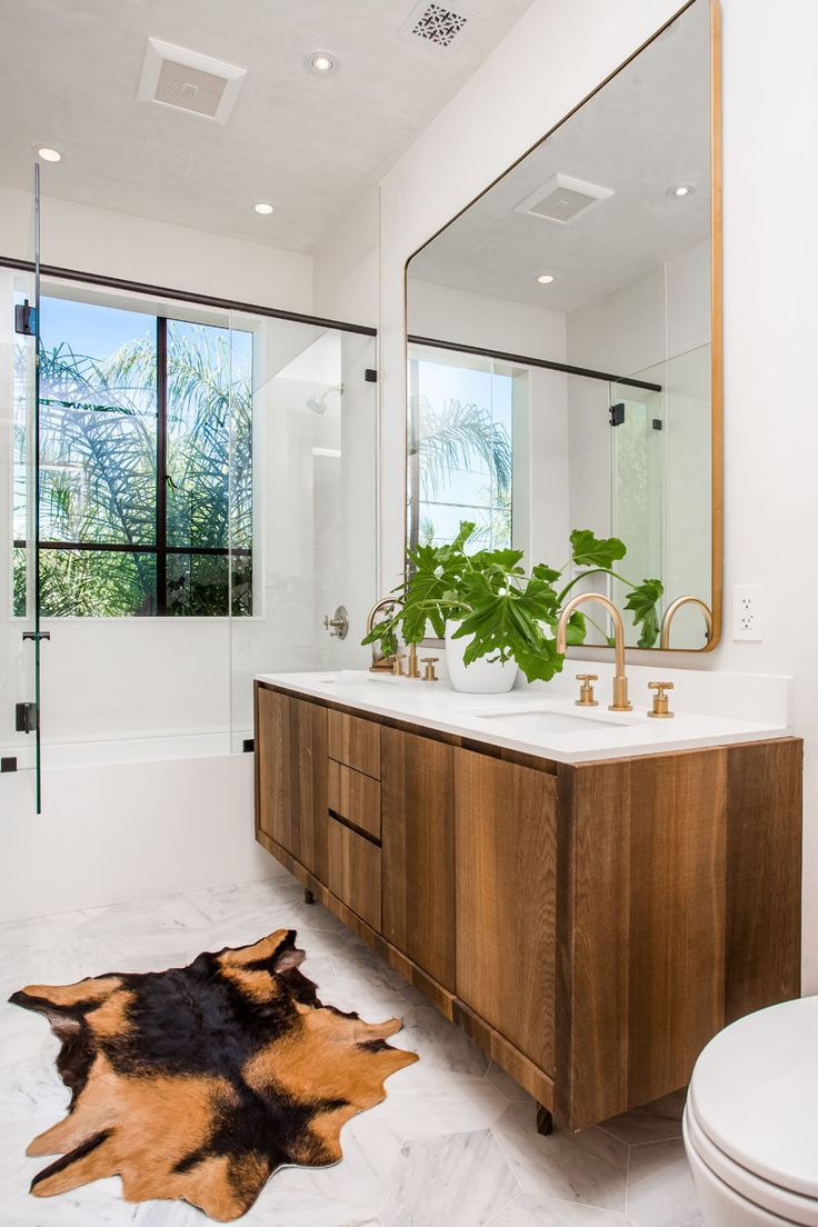 This bathroom combines wooden vanities, gold accents, white walls and plants, to create a contemporary look.