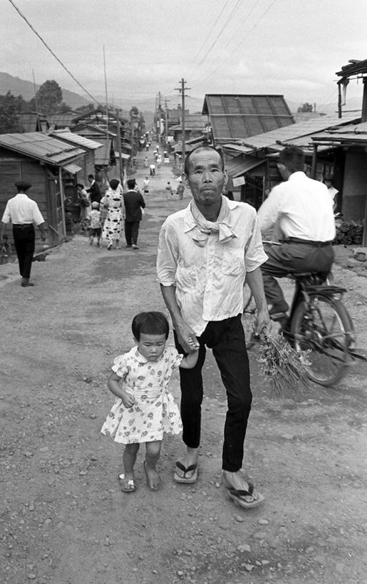 Japanese father and young daughter walking up a dirt road. 1955.