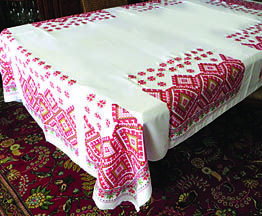 White polyester gabardine fabric tablecloth with red hutsul design. Washable and sturdy.