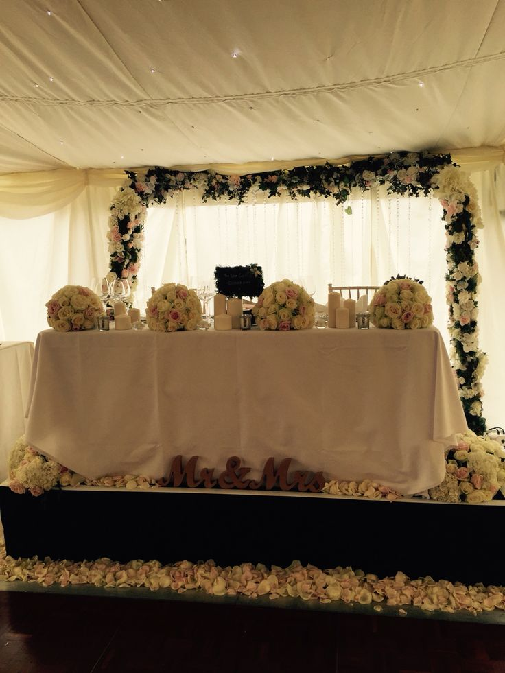 Top table at wedding with floral arch, candles, petals and flowers on the table.