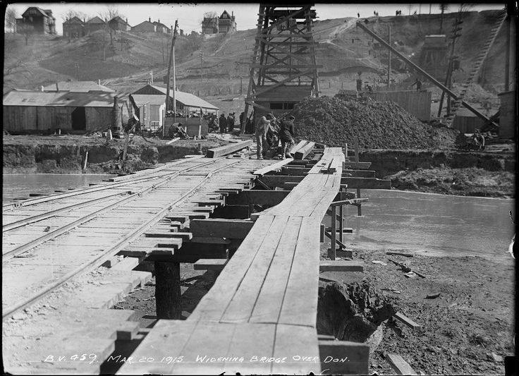Temporary wooden bridge over river leading to excavation equipment and piles of earth.