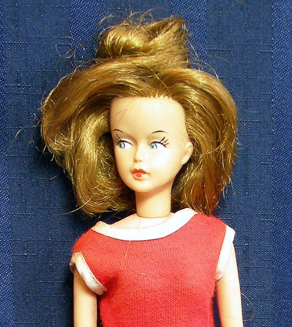 """This is a 1960s Tressy doll. She is wearing her original red dress, but has lost her belt and key. (The key would turn the knob in her back to change the length of her hair.. ) On the back of her head is a mark that says """"American Doll and Toy Corp. c.1963"""" in a circle."""