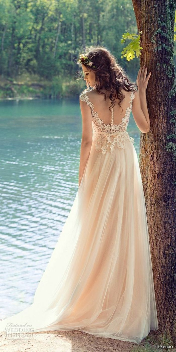 simple wedding dress, young bride with curly dark hair and a small flower crown, with a long cream wedding dress with lace details near the back, one hand on a tree and standing near a woodland lake