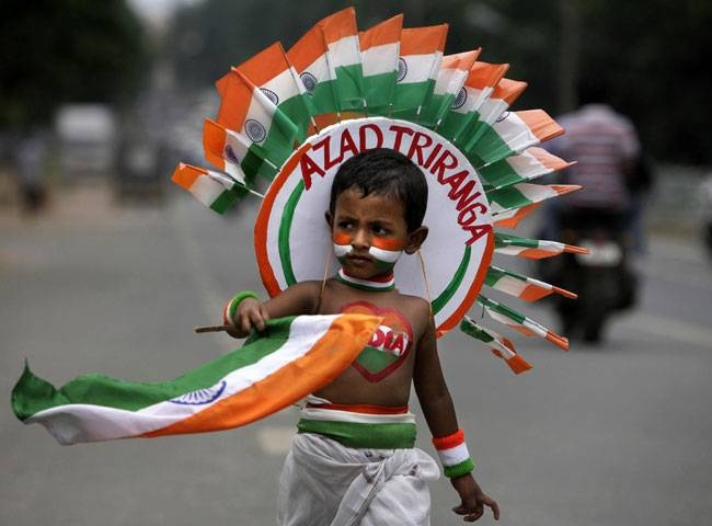 A boy carries the Indian flag as he takes part in a street play during rehearsal for the Indian Independence Day celebrations in Bhubaneswar.