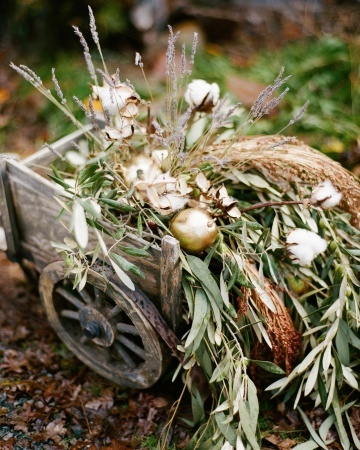 A wooden wheelbarrow overflowing with lush greenery and other decorative elements