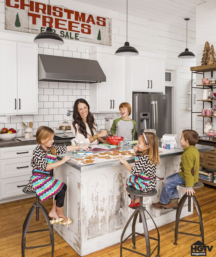 You wouldn't know by looking at it, but the kitchen island is actually a salvaged church altar from the late 1800s. Joanna topped it with stainless steel — the perfect surface material for baking gingerbread cookies with the kids. The cool Christmas tree sign? That was a $50 antique store score!
