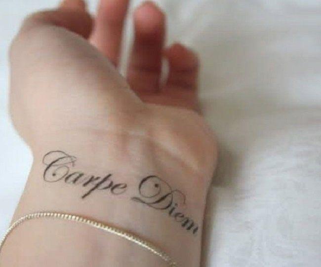 Frase célebre tatuada en la muñeca en una joven mujer