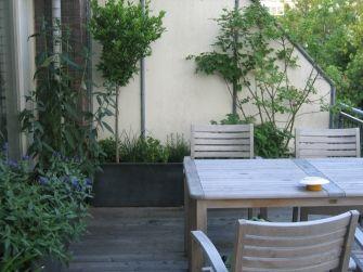 Balkon ontwerp: groen uitzicht vanuit binnen op de daktuin. Bloempotten zijn vervangen door strakke polyester bloembakken