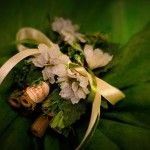 sacchettini in retina verde e avorio con decorazioni di fiori bianchi e legnetti