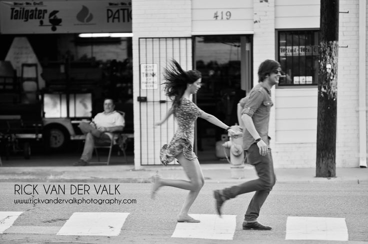 Young couple running during engagement shoot.