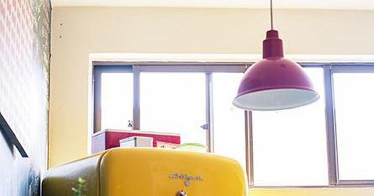 Cozinha com geladeira amarela e luminária divertid