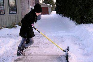Woman shoveling her driveway in winter