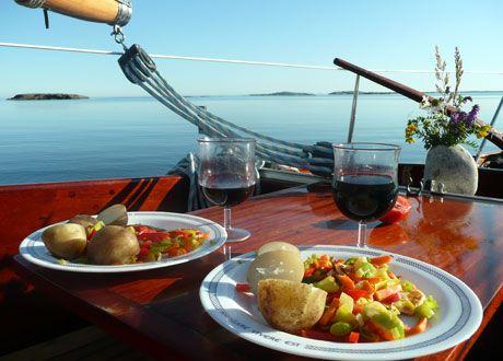 Två tallrikar med potatis och grönsaker uppdukade på bord på segelbåt bredvid två glas rött vin