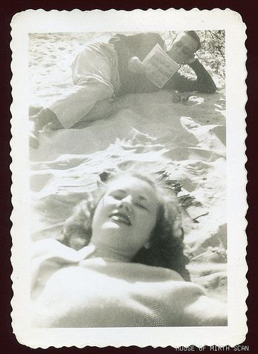 1940s vintage beach photo man reading comics with woman black and white