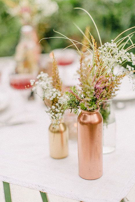 Mix painted copper, gold and clear bottles for a stylish mismatched centerpiece. Source: hochzeits guide. #paintedbottles #diy
