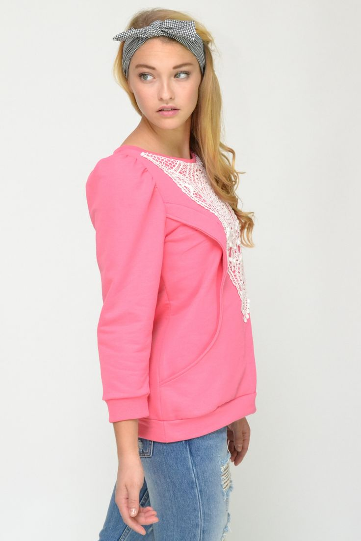 Pink sweatshirt top with intricate white lace detail at front and large side pockets. Slight puff 3/4 sleeves.