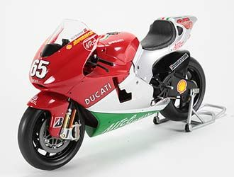 This Ducati Desmosedici (Loris Capirossi - 2006) Diecast Model Motorcycle is Red and Silver and features working stand, steering, wheels. It is made by Ex Mag and is 1:12 scale (approx. 17cm / 6.7in long).    Please note: imperfect outer packaging on this item....