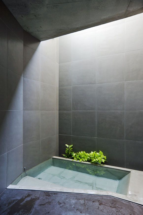 The Art of the Japanese Bath   Sky Garden House  by Keiji Ashizawa Design.  This house for a young family and their parents is located in a residential neighborhood in Tokyo. The bathroom is located beneath the ground, along the sloping street. The enclosed space receives natural light from a top light, which gives the dark-grey-tile-clad room an austere atmosphere.