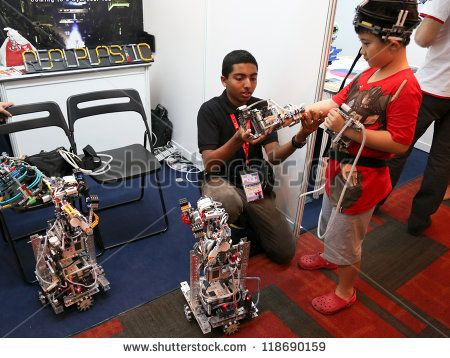 SUBANG JAYA - NOV 10: An unidentified visitor tries out controlling a robot at the World Robot Olympaid on November 10, 2012 in Subang Jaya, Malaysia. This year's theme is robots connecting people.