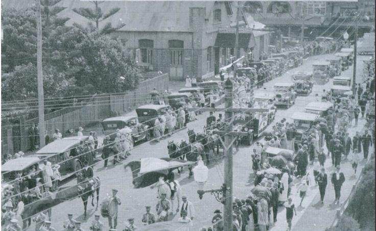 1927 photo of Phyllis Stroud's Surf Queen Parade 26/1/1927 in Surf Road, Cronulla, showing the 1912 School of Arts building (on left) without any shopfronts, with a gabled awning to a central entry in the ground floor façade, and two pairs of French doors to the northern end of the eastern (Surf Lane) façade. Note part of the western extension is visible to the right of the 1912 building.