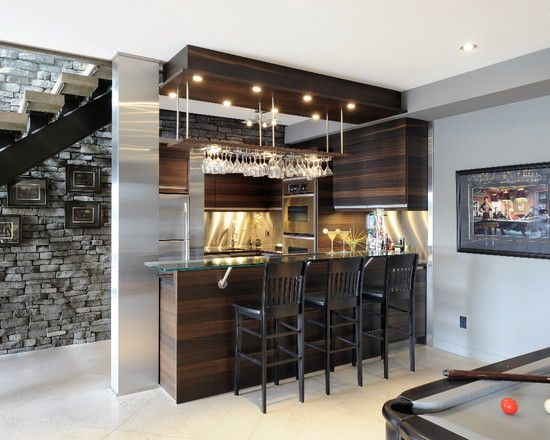 Contemporary style, 'rational' cabinetry Atmos Collection in Bookmatched stripey oak, bog wood horizontal wood grain finish. Stainless steel back splash, antiqued cambrian black stone surface along with glass bartop on stainless step posts, with footrest. Floating (ceiling hung) decorative bulkhead with lighting and wine glass racks.