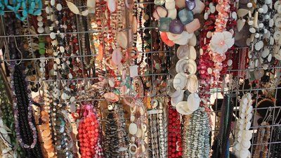 Jewelery from gemstones hanging for sale.