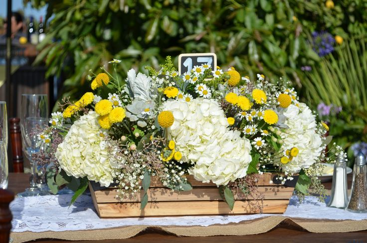 Centerpiece in wood crate of hydrangeas chamomile