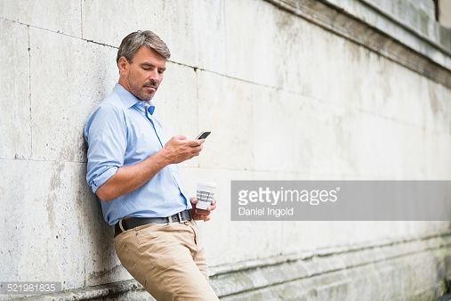 Stock Photo : Mature businessman leaning against wall reading texts on smartphone and drinking takeaway coffee