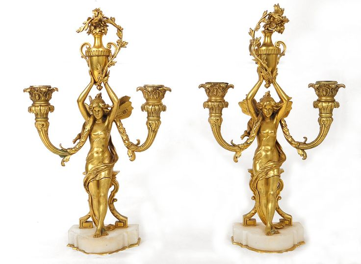 Paire de candélabres à deux douilles en bronze doré finement ciselé, à décor de femmes nues ou nymphes ailées tenant au dessus de leur tête une urne ou amphore fleurie, sur leurs épaule une tige végétale formant les deux feux, socle en marbre blanc, d'époque Napoléon III XIXème siècle.  Ces bougeoirs sont en bon état et sont d'une remarquable qualité et finesse de ciselure. A signaler : le bouquet de fleur au dessus d'une urne bouge un peu (jeu dans le pas de vis de fixation), une bordure de…