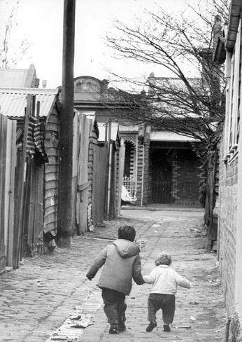 """July 1970: Two young Melburnians play in the back streets of Richmond. The caption found on the back of this picture reads: """"Where the young so often grow up without hope ... an inner-city back street that is home to many of Melbourne's poor - the widow, the unemployed, the unmarried mother and, often the derelict."""" - Melbourne's slums 